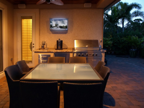 outside kitchen area with a tv and grill